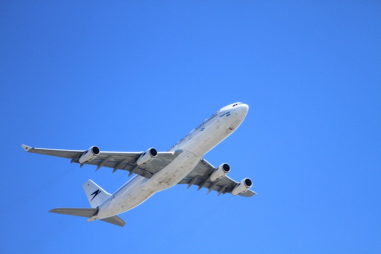 passenger airplane taking off with blue sky in background